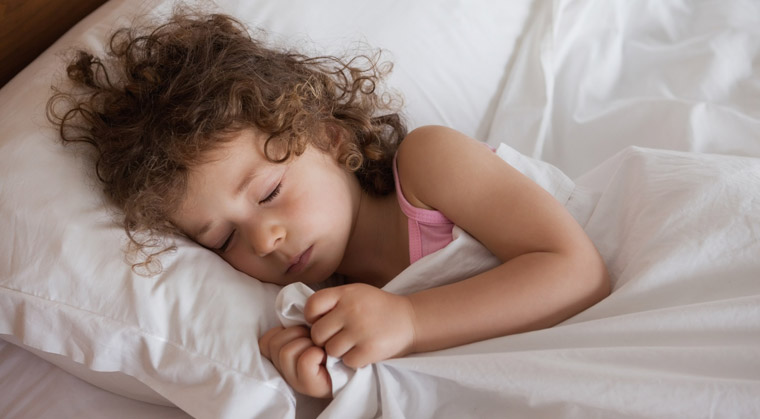 young girl sleeping soundly in bed